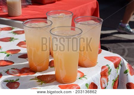 Lemonade stand with drinks of cantaloupe ade ready to serve at farmer's market lemonade stand