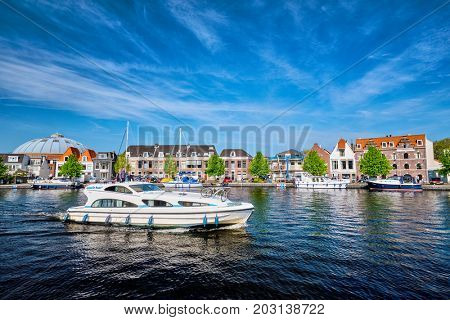 HAARLEM, NETHERLANDS - MAY 6, 2017: Boats and houses on Spaarne river with blue sky. Haarlem, Netherlands