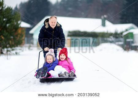Two funny little sisters having a ride on a snow shovel on chilly winter day. Children playing in a snow during winter break. Winter activities for families.