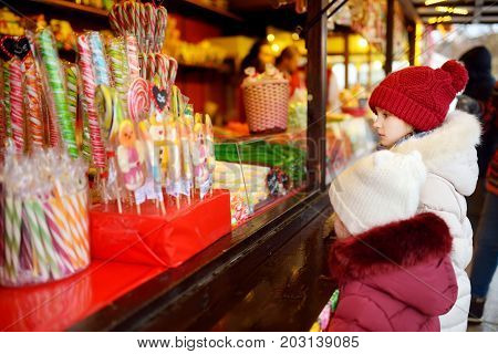 Cute Little Sisters Choosing Sweets On Traditional Christmas Market On Chilly Winter Day.