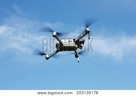 Drone flying with blue sky and clouds as background