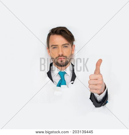 Portrait of young business office man looking at the camera with thumb up while breaking throught the white paper wall