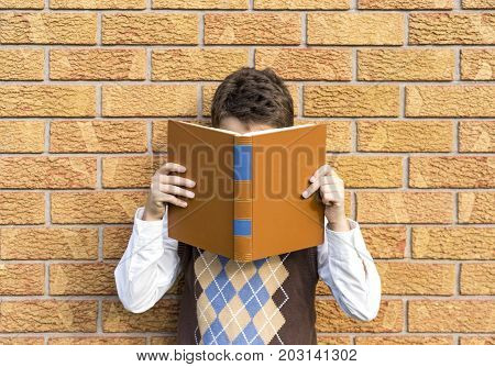Preteen Boy With His Head In A Book, Reading, Wearing A Retro Sweater Vest And Leaning On A Brick Wa