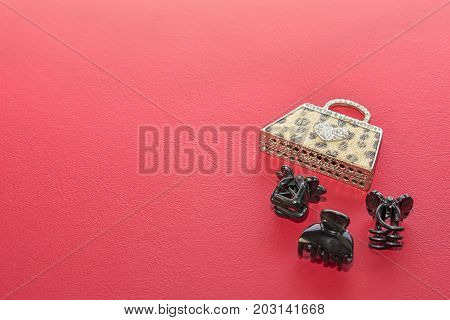 Wallet-shaped key chain and three black clips for the hair. Red background.