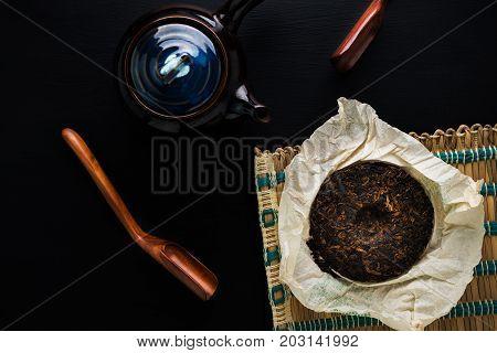 Tea Pot And Green Dry Tea On Black Table