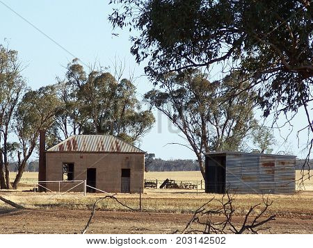 Old clay brick house with corrugated tin roof with wooden shed in dry Australian paddock.