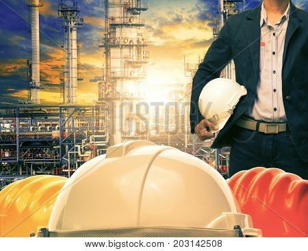 engineering man and safety helmet against oil refinery industries plant