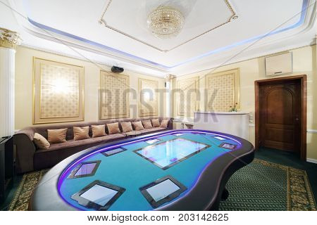 Private empty hall in casino with electronic poker table and soft couch