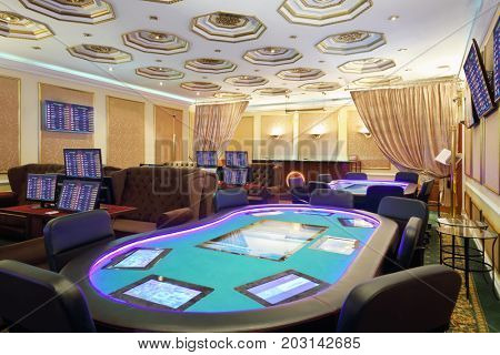 Empty casino with modern electronic poker table and computers for gaming