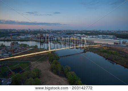 Suspended footbridge Pavshinskaya floodplain evening in Krasnogorsk, Russia