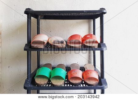 Pairs of home-made traditional wooden shoes on the shoe rack. Wooden clogs are versatile shoes appear in and out of house in olden days.