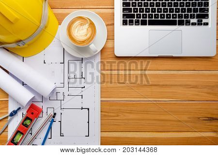 Architect desk project in construction site with blueprintpenlaptop computerhardhatconstruction level calculator and cup of coffee .Top view with copy space.