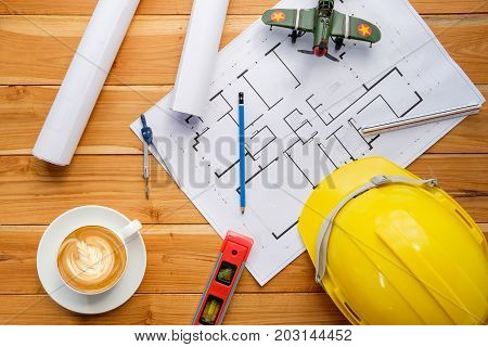 Architect desk project in construction site with blueprintpenhardhatconstruction level and cup of coffee.Top view.