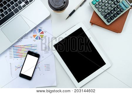Modern white office desk table with laptopnotebooksmart phonefinancial report and cup of coffee.Top view with copy space.Working desk table concept.