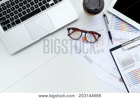 Modern White office desk table with laptop tablet pen eyeglasses and financial report.Top view with copy space.Working desk table concept.