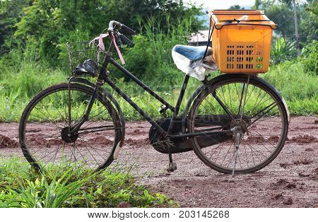 old bicycle and orange basket on soil and mud road in countryside in morning after raining in last night