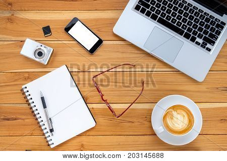Office desk table with laptopblank screen smart phonenotebook and cup of coffee.Top view with copy space.Working desk table concept.