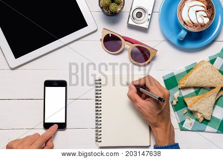 Man using smart phone and writting notebook in white desk.Hand holding smart phone white white screen.Top view