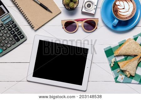 Modern White office desk table with tablet computerleather notebookcalculator and cup of coffee.Top view with copy space.Working desk table concept.