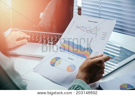 Businesswoman analyzing investment charts with laptop computer on office desk table.Close up.Financial Report Revenue Statistical Accounting Concept.
