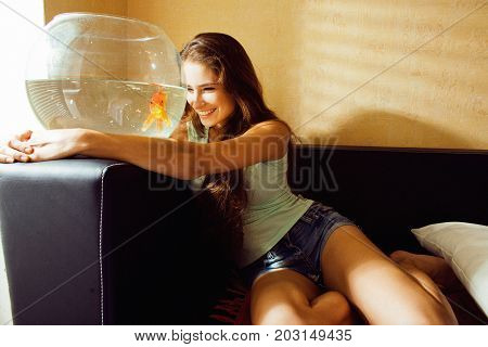 pretty woman playing with goldfish at home, sunlight morning smiling