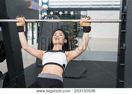 Young Woman Execute Exercise With Weightlifting Machine In Fitness Center. Female Athlete Pump Up Mu