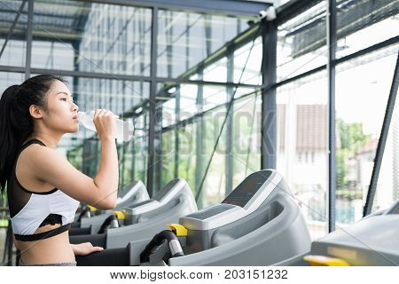 Young Woman Drinking Water In Fitness Center. Female Athlete Feeling Thirsty After Training In Gym.