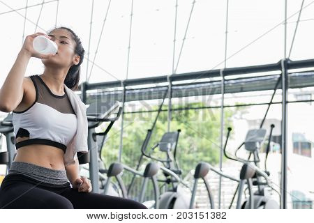 young woman drinking water in fitness center. female athlete feeling thirsty after training in gym. sporty asian girl taking a break from working out in health club. poster