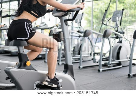 Young Woman Execute Exercise In Fitness Center. Female Athlete Riding Stationary Bicycle In Gym. Spo