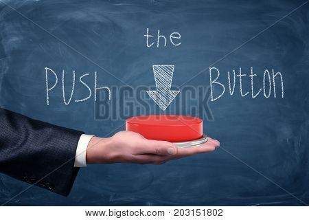 A large red push button resting on businessman's palm under a chalkboard drawing saying Push the Button. Start your business. No delays. Do it now.