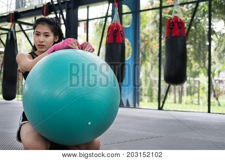 Young Woman Execute Exercise In Fitness Center. Female Athlete Posing With Ball In Gym. Sporty Girl