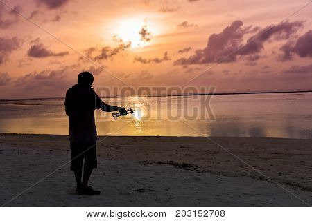 Silhouette Man Operating The Drone By Remote Control On Beach At Maldives Island