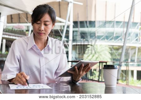Businesswoman With Digital Tablet & Financial Summary Graph Sitting Outside Office Building. Young A