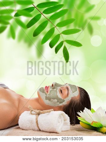 Young healthy woman in spa making treatments and face mask.