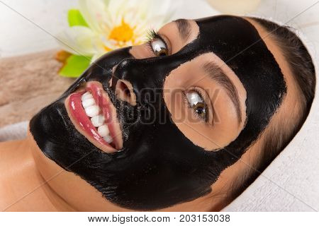 Young healthy woman in spa with black anti pore face mask.