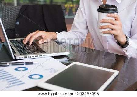 Businesswoman With Laptop Computer & Financial Summary Graph Sitting Outside Office Building. Young