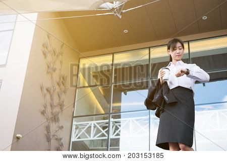 Businesswoman In A Hurry Holding Coffee And Looking At Her Watch Outside Office Building. Young Asia