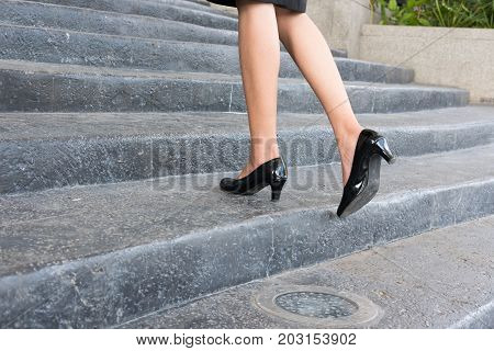 Feet And Leg Of Businesswoman Wearing Black High Heel Shoes Going Up The Stairs Outdoors. Woman Go T
