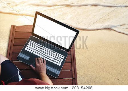 a man using computer laptop on wooden sunbath lounge chair on the beach in summer at sunset. Clipping path computer notebook screen