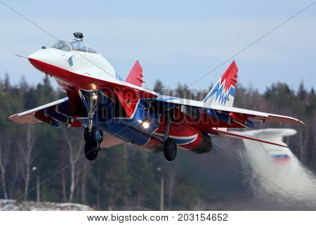 Kubinka, Moscow Region, Russia - February 19, 2014: Mikoyan Gurevich MiG-29UB 11 BLUE jet fighter of Strizhi The Swifts aerobatics team taking off at Kubinka air force base.