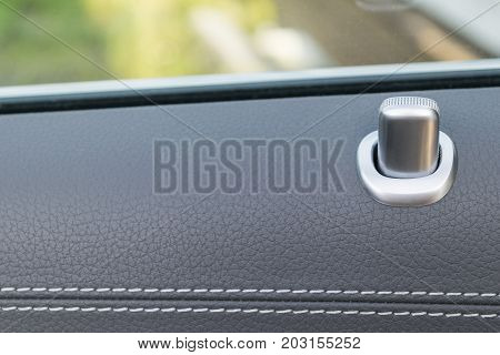 Door handle with lock contol buttons of a luxury passenger car. Black leather interior of the luxury modern car. Modern car interior details