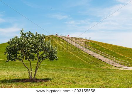 VIRGINIA BEACH, VIRGINIA - JULY 10, 2017:  People exercise at Mount Trashmore Park, the site of a former landfill which was converted to a city park in 1974.