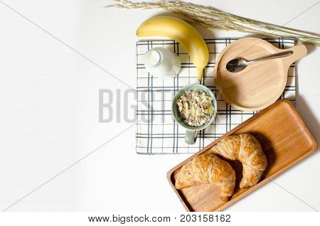 Breakfast with Croissant and Muesli and banana and fresh milk in white background on the table