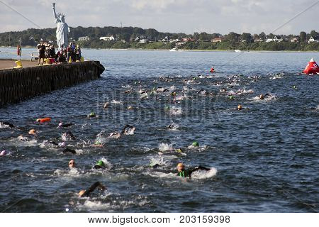 Fredericia Denmark - September 3 2017: Triathletes swimming the triathlon competition Challenge Denmark in Fredericia Harbor. Artist Jens Galschiøt Statue of Liberty at the harbor.