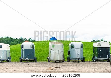 Many horse trailers in the green park. Outdoors.