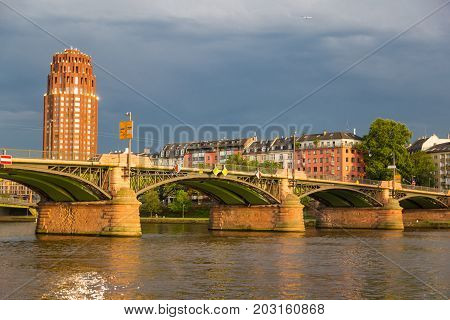 Bridge Floesser across the river Main at sunset. View of the bridge and houses on the waterfront. Frankfurt am Main city. Germany