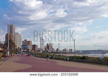Paved Promenade Against Beachfront Cloudy City Skyline Landscape