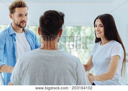 Non standard therapy. Joyful nice positive people smiling and looking at each other while having a psychological session