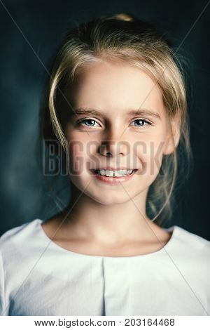 Close-up portrait of a cute eight-year-old girl smiling at camera.