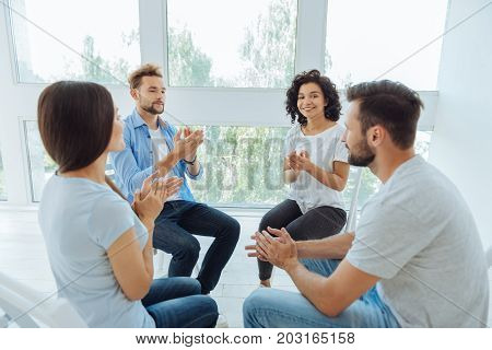 Mini group. Positive nice delighted people sitting in the circle and applauding each other while having a psychological therapy session